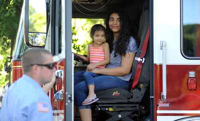 9/24/2016 Mike Orazzi | Staff Sisters Viangelique and Audrie Rivera sit in the driver's seat of a Bristol Fire Department truck during the Bristol Mum Festival on Saturday on Memorial Blvd.
