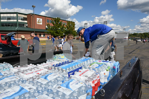 09/08/17 Wesley Bunnell | Staff A Pack the Truck event for Hurricane Harvey relief took place on Friday afternoon in the parking lot at New Britain Stadium. The event was a partnership between the New Britain Bees, Houston Astros outfielder George Springer, Siracusa Moving and Storage, A1 Automotive Repair, the Connecticut Blue Jays AAU Travel Team and Premier Limousine with trucks from Siracusa leaving for Houston following the event. CCSU Baseball student athlete Nick Garland stands in the truck to unload donations with the help of women lacrosse team member Meaghan Allard. The truck bed full of bottled water was donated by Elohim Casa De Dios of Meriden.