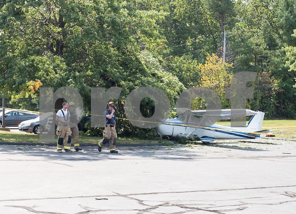 09/11/17 Wesley Bunnell | Staff A small plane crashed Monday morning near Robertson Airport in the parking lot of Carling Technologies at 60 Johnson Ave in Plainville. Firefighters walk past the scene.