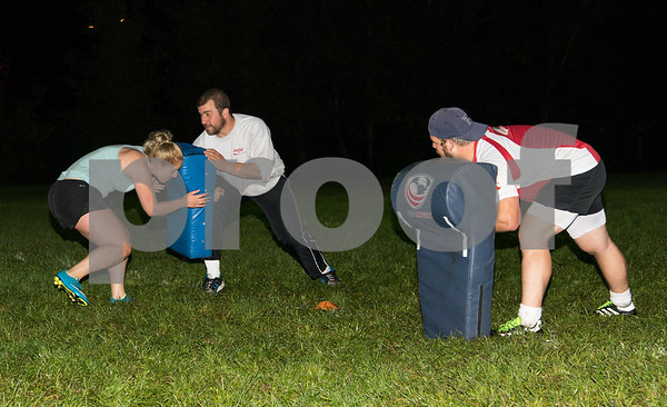 09/06/17 Wesley Bunnell | Staff CCSU women's rugby held their first practice on Wednesday September 6 after an almost 10 year absence. Junior Lexie Cousino hits the pad being held by mens rugby team coach Shawn Panik as womens team coach Kevin Potter looks on.