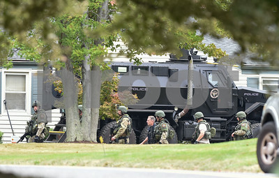 09/21/17 Wesley Bunnell | Staff  SWAT members walk past a Newington Police armored vehicle on Gilbert Rd on Thursday afternoon at the end of a police standoff.