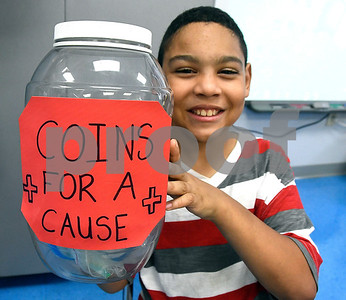 9/27/2017 Mike Orazzi | Staff Julio Rodriguez holds a jar used to raise $1057 for recent hurricane victims at the South Side School in Bristol.