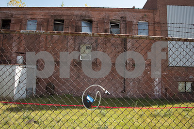 09/26/17  Wesley Bunnell | Staff  The former steam house at Stanley Black & Decker on 95 Curtis St which is undergoing demolition. Water is being sprayed onto the building during demolition with asbestos warnings visible and air quality monitors hanging from the perimeter fencing.