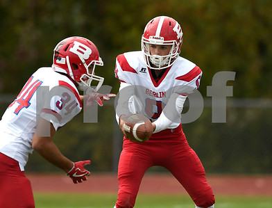 9/30/2017 Mike Orazzi | Staff Berlin's Kevin Dunn (9) hands off to Alexander Halkias (34) during Saturday's football game in Hebron.