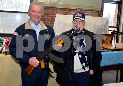 1/14/2015  Mike Orazzi | Staff David Peplau and Jake Comeau hold an AK-47 at the Bristol Memorial Military Museum on Federal Hill in Bristol.