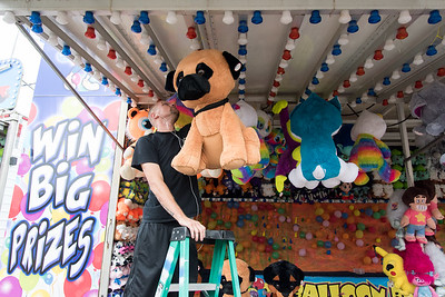 09/13/18  Wesley Bunnell | Staff  Patrick Tillman hangs large stuffed animals to be won in front of the balloon bust game on Thursday afternoon while setting up for opening night at the Berlin Fair.
