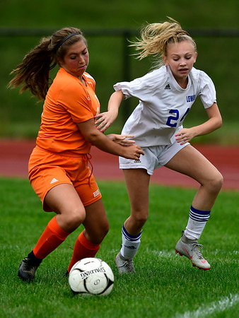 9/13/2018 Mike Orazzi | Staff Lewis Mills' Amy Crossman (24) and Terryville's Lena Stefano (9) during Thursday's soccer at THS.