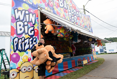 09/13/18  Wesley Bunnell | Staff  Patrick Tillman carries large stuffed animals to be won at the balloon bust game on Thursday afternoon while setting up for opening night at the Berlin Fair.