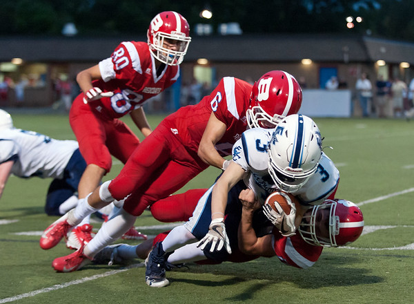 09/13/18 Wesley Bunnell | Staff Berlin football vs East Catholic at Sage Park on Thursday night. John McGeever (6) assists on the tackle.