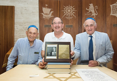 09/05/18  Wesley Bunnell | Staff  A plaque honoring the late Rabbi Henry Okolica is held by Congregation Tephereth Israel Board Treasurer Fenmore Feigenbaum, Vice President Daniel Price and Secretary Murray Zinman. The Sanctuary at Congregation Tephereth Israel will be dedicated to Rabbi Okolica in a ceremony at 10:00 a.m. on September 10th. The three men with the help of President Elliot Cohen, not present, worked together to make the plaque and dedication a reality.