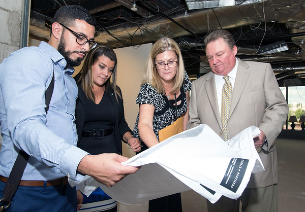 09/05/18 Wesley Bunnell | Staff Architect Arturo Arroyo from Svigals & Partners looks over blueprints with Mayor Erin Stewart, CMHA Executive Vice President & CFO Mary Gilhuly and TBI Constructions Ken Johson detailing upcoming renovations to CMHA's newest building located at 233-235 Main St on Wednesday afternoon. The building will undergo renovations in preparation for CMHA's occupancy which was previously planned for 227 Main St.