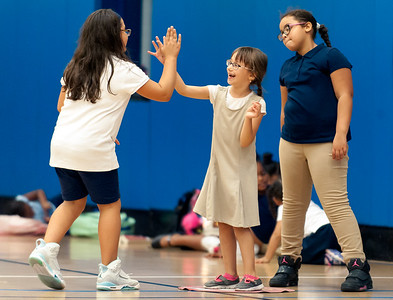 09/06/18  Wesley Bunnell | Staff  Nellie Djakun, middle gets high fived standing on first base by Leighani Padilla, L, as Javlieanie Sierra looks on during a game of kickball at the Boys & Girls Club of New Britain on Thursday afternoon. The club's after school programs have opened earlier than normal to accommodate school children during the CSDNB's decision to start the school year off on half days due to excessive heat.