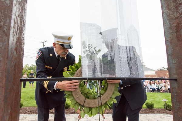 09/11/18 Wesley Bunnell | Staff Berlin officially dedicated its 9/11 Memorial in front of the Kensington Fire Department on Tuesday afternoon featuring steel beams from the World Trade Center. Friend of Berlin Fire Department New Britain Deputy Chief Paul Walsh, L, helps place a wreath with his son Kensington Firefighter Tyler Walsh.