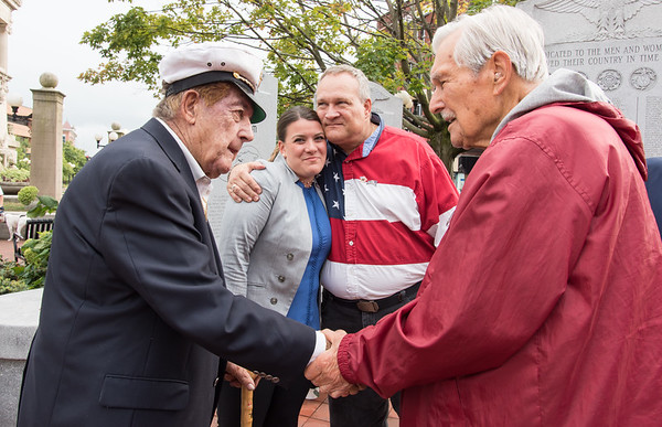 09/11/18 Wesley Bunnell | Staff New Britain unveiled its newest monument in Central Park which is dedicated to the War on Terror following the 9/11 attacks. WWII Veterans Peter Spano, L, and Fred Peterson shake hands as Mayor Erin Stewart receives a hug from Peterson's son Roger Peterson.