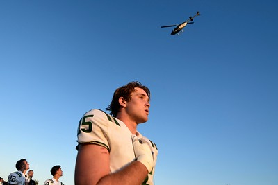 De La Salle players glance up as a helicopter performs a fly-over after the singing of the national anthem before their game at Central Catholic High School in Modesto, Calif. on Friday, Aug. 30, 2019. (Jose Carlos Fajardo/Bay Area News Group)