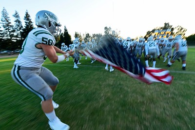 De La Salle's Jon Puckett (50) waves the U.S. flag as the team runs onto the field before their game at Central Catholic High School in Modesto, Calif. on Friday, Aug. 30, 2019. (Jose Carlos Fajardo/Bay Area News Group)