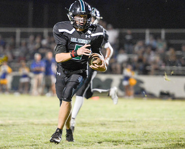 Biggs' quarterback Gregg Slusser takes off with the ball during the Wolverines' game against the Braves on Aug. 30 in Biggs. (Matt Bates -- Enterprise-Record)