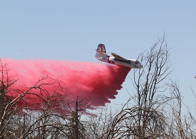 A fire fighting plane drops retardant Friday along the area surrounding the Forbestown Fire near Oroville. (Jake Hutchison -- Enterprise-Record)