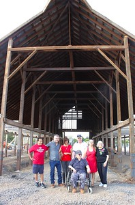 Family members pose Saturday in front of the old DeMeyer barn, which was taken down in 2017 from its original location on Meridian Road and West Sacramento Avenue, and is now being reassembled in Meriam Park. Shown are Andy Ramirez, Greg DeMeyer, Dianne Suschil, Chris DeMeyer, Sharon DeMeyer, Dayle Perry, and Ray DeMeyer in the foreground. (Steve Schoonover -- Enterprise-Record)