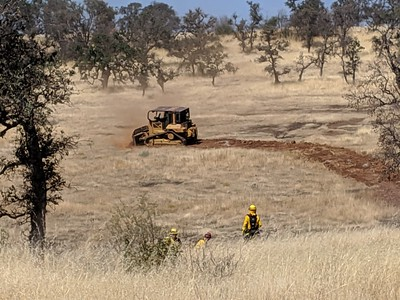 A bulldozer blocks the fire's path Thursday on Neal Road north of the landfill. (Jake Hutchison -- Enterprise-Record)