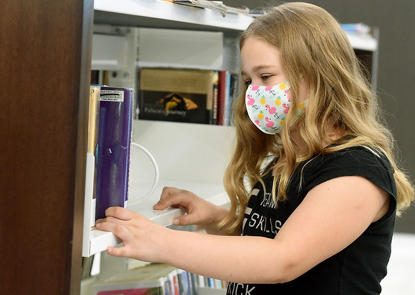 Eight-year-old Rori Welch looks through the selection of children's books on Thursday at the Joplin Public Library. The library is currently operating on a modified schedule, opening at 10 a.m. Monday through Saturday. They close at 6 p.m. on Tuesdays and Fridays and 3 p.m. on Mondays, Wednesdays, Thursdays and Saturdays. Globe | Laurie Sisk