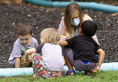 Teacher's aide Elizabeth Dart plays with kids on the rubber mulch surface on one of the playgrounds at South Joplin Head Start on Thursday. From the left: Silas Stanley, 3, Adelyn Smith, 4 and Emmanuel Sang, 4. Globe | Laurie Sisk