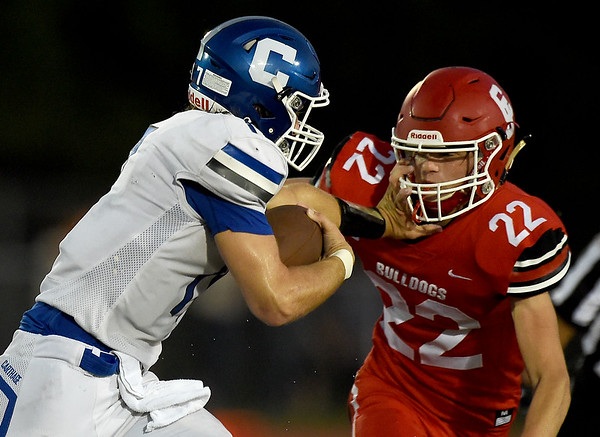 Carthage quarterback Patrick Carlton (17) tries to get past Carl Junction linebacker Carter Kennedy (22) during their game on Friday night at CJHS. Globe | Laurie Sisk