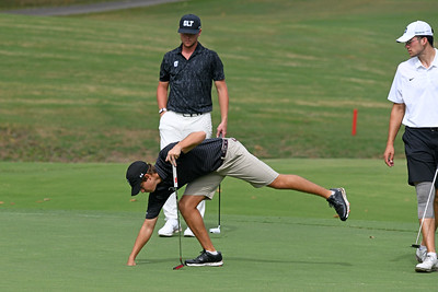 With Dartmouth and Charlotte (UNCC) players looking on, Davidson junior Ethan Hall retrieves his ball after sinking the putt.