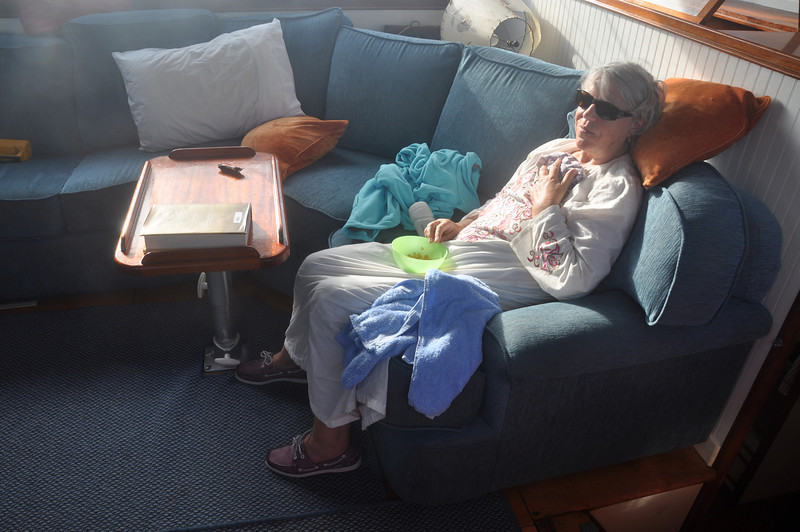 Sheila's dark glasses helped her to feel better. She's sitting on the settee which later became detached from the floor in the swell catapulting Ian across the lounge. Behind the settee was Yogi's secret biscuit store as rations on board were limited