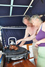 BBQ Chef Graham and Ann inspect the leg of lamb for Sunday lunch onboard Serengeti