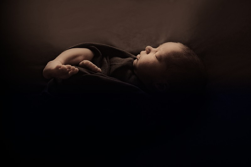 the concept of healthy lifestyle, IVF - a newborn baby sleeps under a blanket. Head, legs and arms
