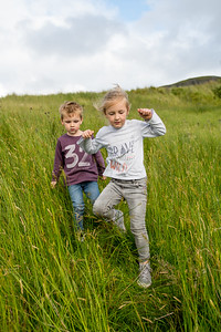 portrait Happy Young boy and girl jogging running in tall grass in ireland irish nature on an adventure hike in summer.
