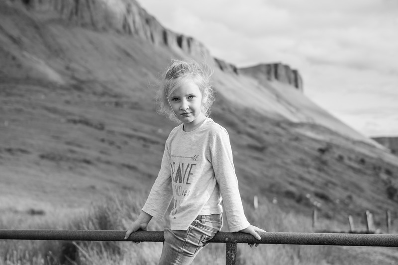 Happy girl swinging standing on a farm gate. black and white