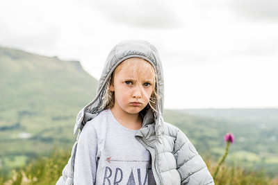 girl with hoody hiking with a sad face.