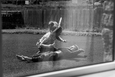 boy and girl playing out in front of house.  playing childrens games like DR and other things children do when learning and discovering.