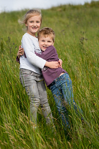 Happy Young boy and girl smiling holding hands in nature on an adventure hike in summer.