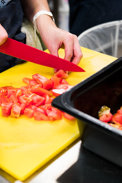 A chef is chopping tomatoes on a yellow cutting board.