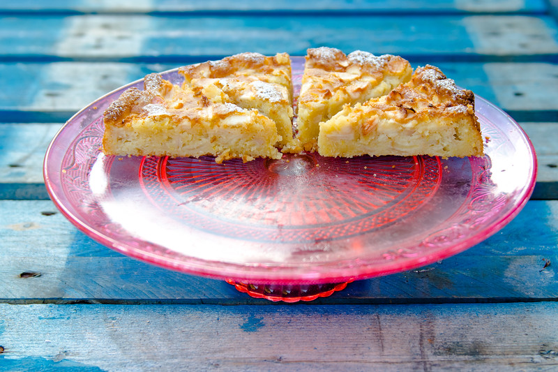 Slices of half an Apple, pear, almond tart cake on a glass red desert plate.