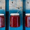 Rustic home made Raspberry, Strawberry, red berry jam filled jars sitting on a picnic table.