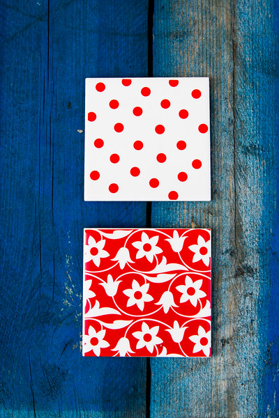 Colorful red and white tile patterns on tiles sitting on a blue picnic crate palette table.