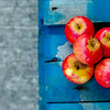 Bright red farm apples on a blue picnic table.