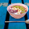 Healthy fruit salad with banana, almonds, kiwi, tropical fruits, chia seeds, vegan breakfast in a retro bowl.