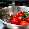 Fresh red tomatoes in a metal commercial kitchen bowl.