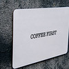 Board paper displaying the words Coffee First with a rough textured background.
