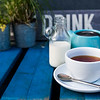 A white coffee cup and saucer with a blue tea coffee pot on a blue picnic table.  The words eat and drink are painted on a wooden plank.