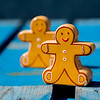 Gingerbread figures sitting on a blue picnic table.