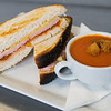 A grilled ham and cheese sandwhich with tomato soup in a teacup.