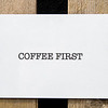Board paper displaying the words Coffee First on a wooden crate.