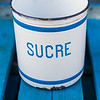 A vintage white bucket with sucre sugar written on it sitting on a blue picnic table.