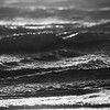 Water crashes on the beach during a red sunset.  Close up image of water rolling on an illuminated beach in Ireland. Black and White